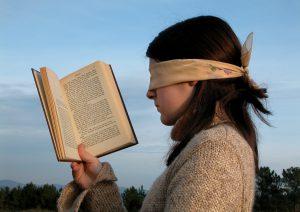 femme lisant un livre à voix haute les yeux bandés